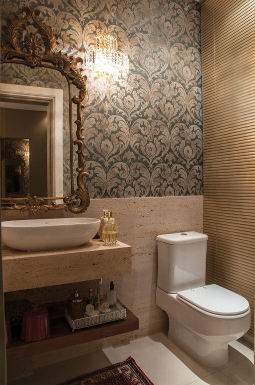 """O lavabo exibe ambientação igualmente elegante. """"A cliente desejava uma composição luxuosa"""", explica Arlon. Travertino romano bruto forma a bancada e cobre meia parede, valorizando o papel de parede de tom azulado. Persiana dourada e espelho com moldura em bronze."""
