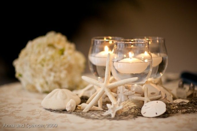 Candle and shell centerpiece on pearl caviar beaded linens.