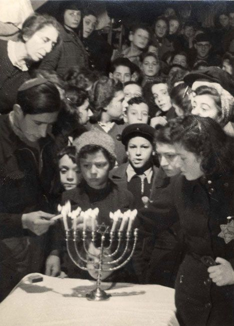 December 1943:  A Hanukkah candle lighting ceremony on the 7th night of Hanukkah in the Westerbork transit camp, Netherlands