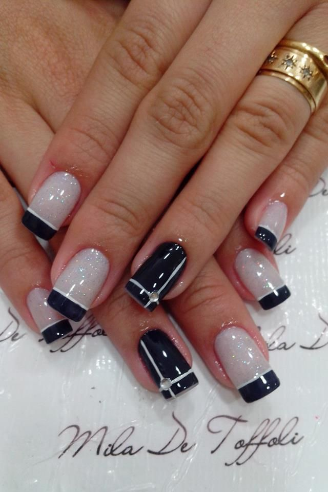Pale, shimmery grey/nude with black and white french tips; black base with white cross and rhinestone detail on accent nails.