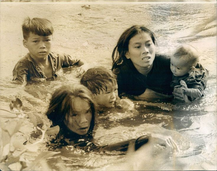 The tragedy of the Vietnam war is graphically illustrated in this picture of a Vietnamese woman and her children wading across a river to escape bombs raining from U.S. planes during an air strike on their village near Qui Nhon. Planes were called in to knock out Viet Cong snipers who were firing on U.S. Marines from the village. This picture was selected by United Press International as one of the best of the year. - UPI PHOTO BY STAFF PHOTOGRAPHER KYOICHI SAWADA 12-9-65