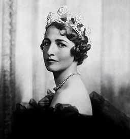 Portrait of Nancy Lancaster dressed for the 1935 Silver Jubilee Ball at Buckingham Palace. She is wearing the Astor tiara borrowed from her Aunt Nancy, Lady Astor, with its famous Sancy diamond worn by Charles the Bold at the Siege of Nancy in 1476. Nancy Lancaster (1897 –  1994) was a 20th-century tastemaker & the owner of Sibyl Colefax & John Fowler, an influential British decorating firm that codified what is known as the English country-house look.
