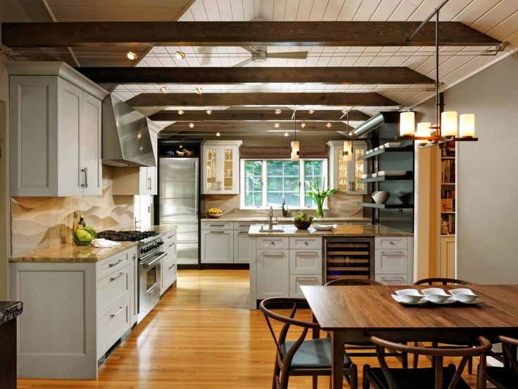The floating beams unify the ceilings and the parallel track lighting to bring the space together harmoniously. The kitchen has a spacious open cooking area, a central prep zone and an additional coffee station for a household that loves its caffeine!