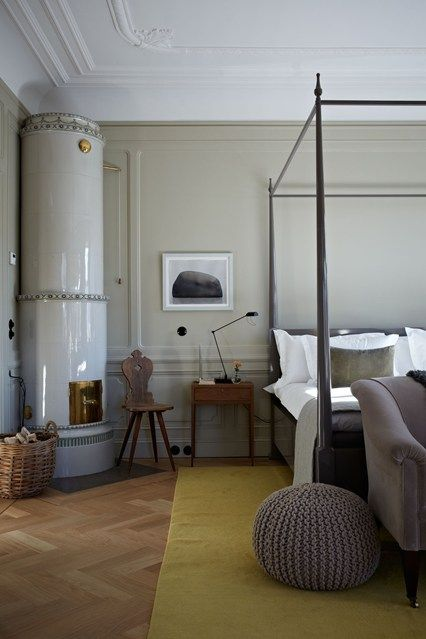 View stylish new ideas for the bedroom. Ett Hem in Stockholm with traditional Swedish wood burning stove and four-poster bed.