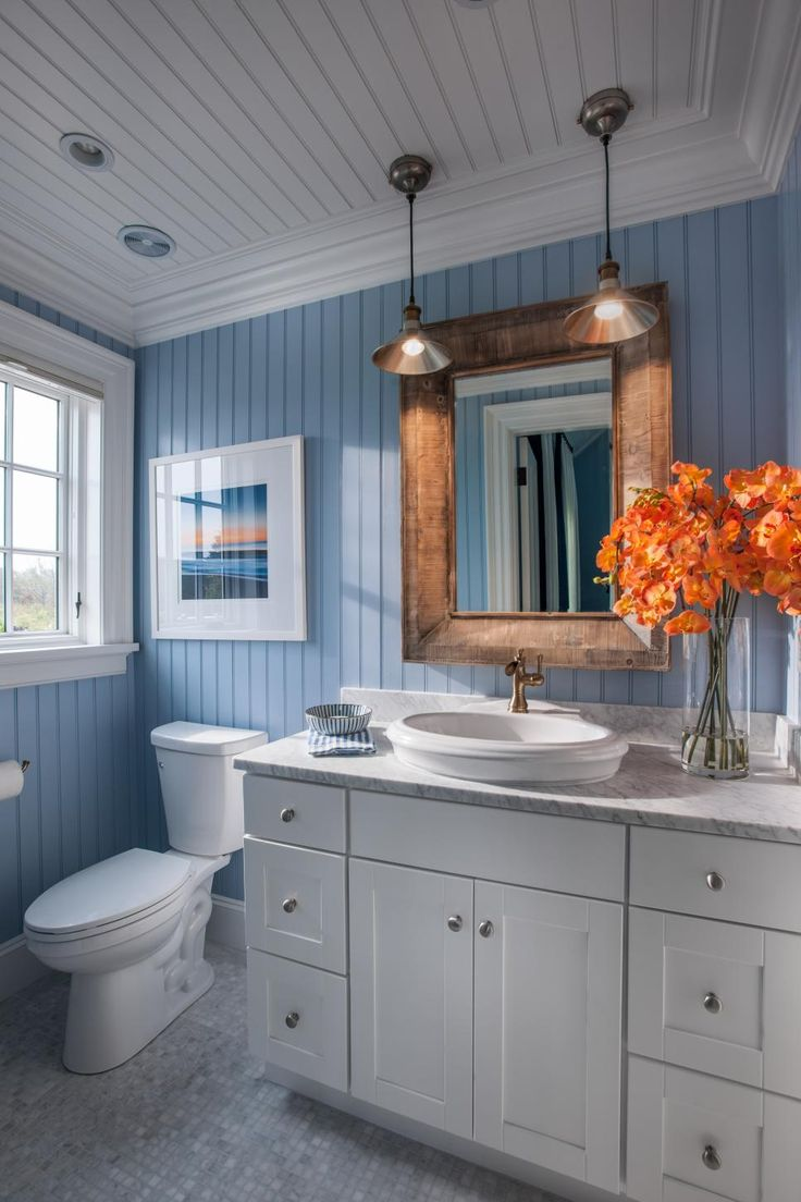 Bright floor-to-ceiling beadboard and a decorative mirror lend whimsical qualities to this kid-friendly bath.