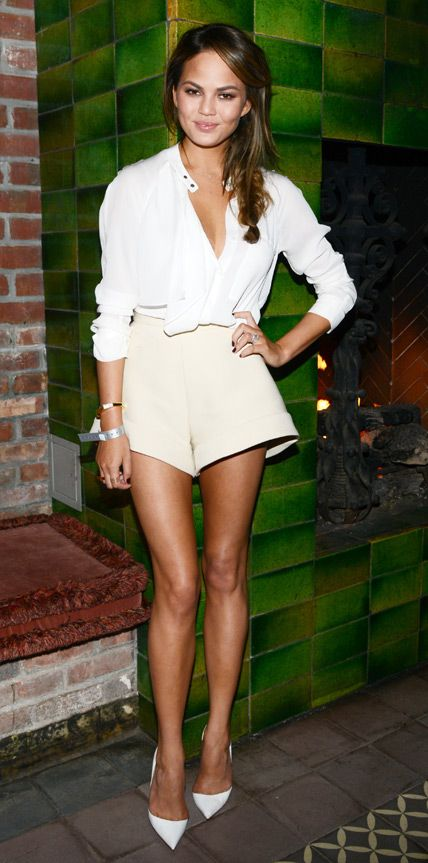 Chrissy Teigen showed off her enviably long, lean legs with tailored cream shorts that she teamed with an optic white A.L.C. blouse, jewelry by EF Collection and Vita Fede, and white pumps.