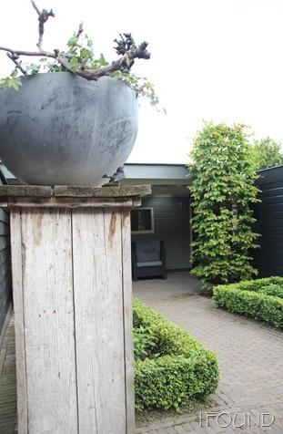 zuil van steigerhout met grijze pot - sokkel in de tuin