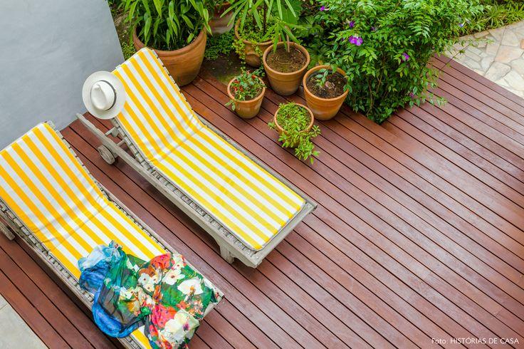 Deck de madeira com composição de vasos de barro e espreguiçadeira com estofado amarelo.