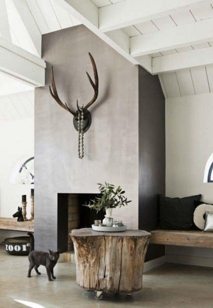 Door gebruik van betonverf, gewei en houten tafel dus gebruik van natuurlijke materialen gecombineerd met egale afwerkvloer. Mooie balk aan zijde van haard.