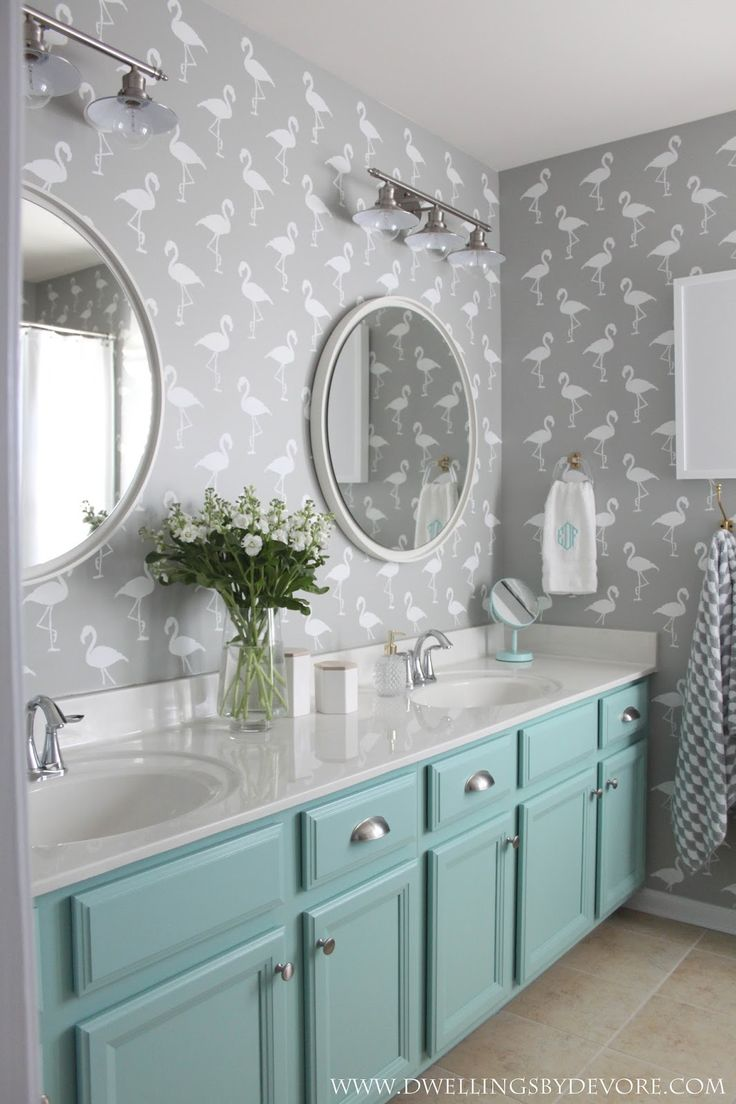 gender neutral kids bathroom with stenciled flamingo walls and painted vanity