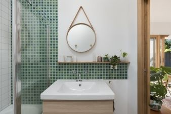 Green tiles from the shower run along the sink to create a splashback