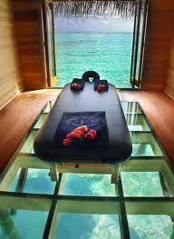 A massage hut in Bali overlooking the crystal waters, clear glass floor to watch the fish while getting a massage.