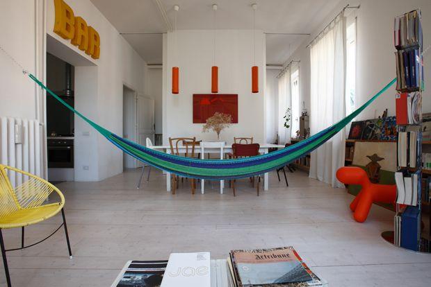Il soggiorno, arredato con un'amaca guatemalteca, tavolo Norden di Ikea, mobili e oggetti di recupero. Le lampade arancioni, realizzate con dei pluviali, sono opera del padrone di casa