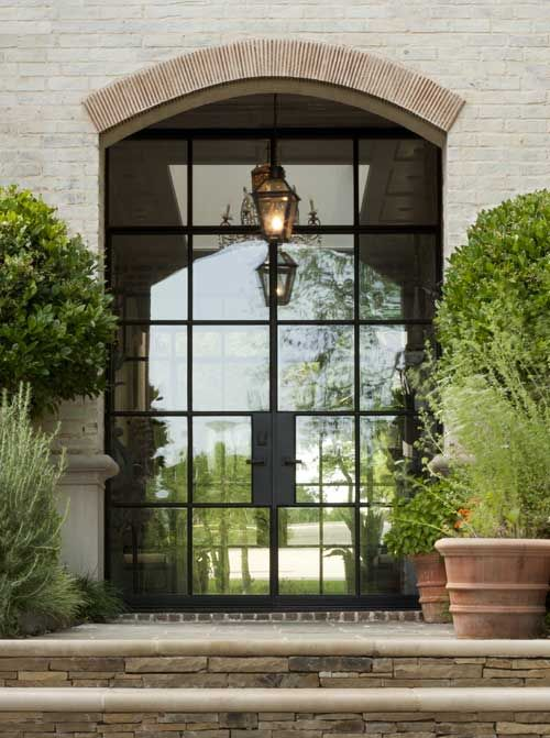 Portella Iron Doors- lovely height/width proportion and arch, love the cut stone under the cast stone smooth steps