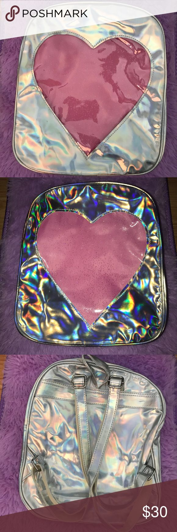 Holographic Heart Backpack Brand new in original packaging. Holographic Transparent Heart Glitter Backpack. Material is faux leather. Not unif. The transparent window shows whatever you put in that area, not everything in the backpack. Very roomy. Can fit lots of water bottles, clothes, notebooks.  Tags: festival, rave, ravewear, Coachella, beyond wonderland, ultra, insomniac, dreamstate, dollskill, little black diamond, j valentine, iheartraves, edc UNIF Bags Backpacks