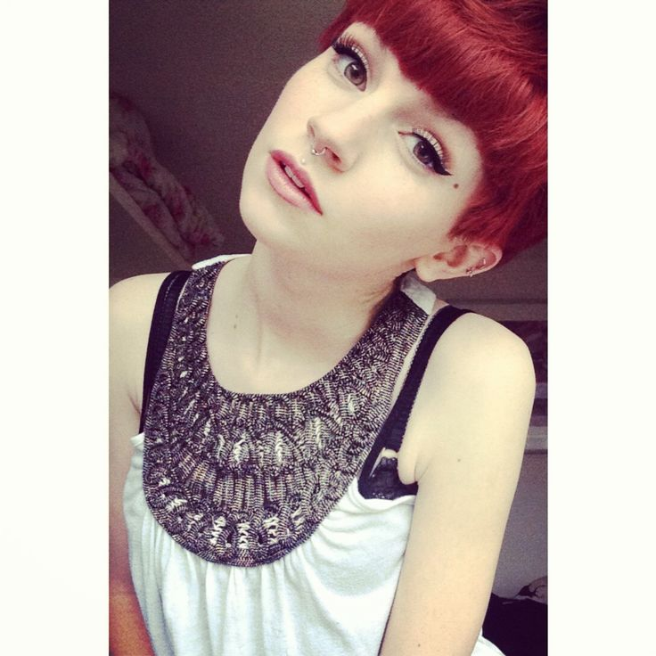Short, red angular hair, liquid eyeliner, pale lipstick, fabulously exposed bra - Why is this chick not a model (I think)?!