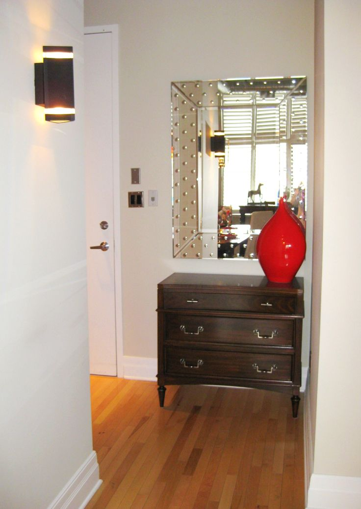 This lovely chest not only fits perfectly beside the front door but it is also practical to 'catch all' and hide it in the drawers.The stylish polka dotted mirror reflects the light from across the room and the bright red vase is the finishing touch.