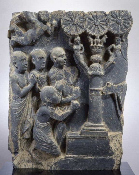 """A sculpture named Expounding the Law, 2nd century. It is at The Art Walters Museum. The three wheels from the top constitute a """"Wheel of the Law."""" The hand on the right side is the hand of the buddha. He is explaning the theaching to his five disclipes by using the pillar as an instructional device."""