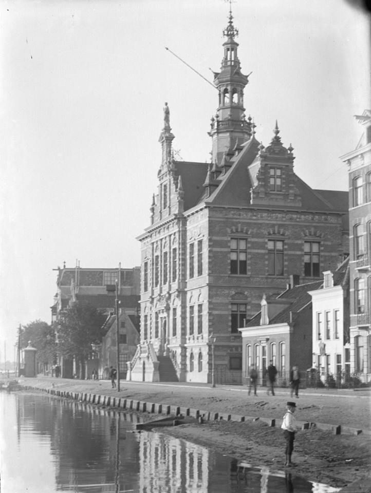 Amsteldijk met het gemeentehuis van Nieuwer-Amstel en aan de linkerzijde het tolhek, 1892.   Nieuwer-Amstel werd in 1795 gevormd en betrof een groot gebied (tot 1964 was Nieuwer-Amstel de naam van de gemeente Amstelveen). In dit gebied ontstond Amstelveen als een dorp in het turfwinningsgebied ten westen van de Amstel. Verder behoorden ook de dorpen Bovenkerk, Nes aan de Amstel en het op de linker... Meer weergeven