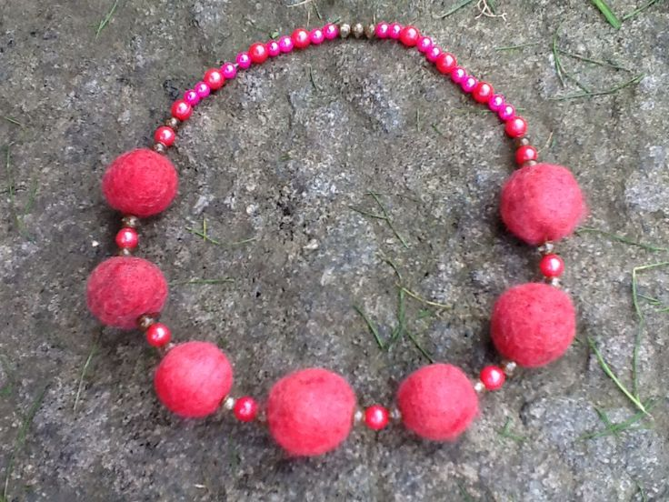 Halsband av pärlor och tovade små bollar.