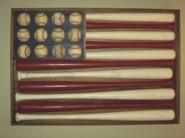 "Another baseball flag.  If you wanted to save money and you had the tools, you could put the bats through a table saw and cut them in half to give you more bang for less ""buck"". man-cave-ideas-diy"