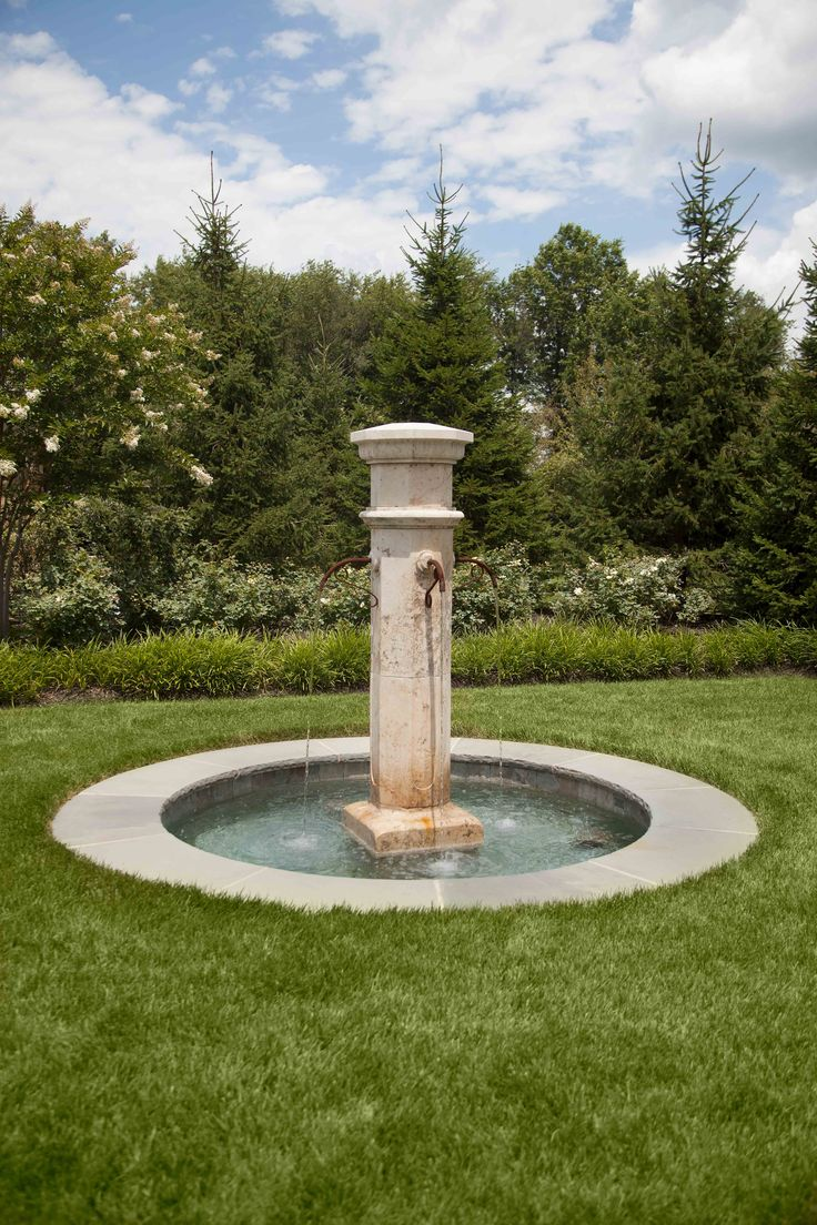 This French-country fountain serves as a focal point in a transitional space within this landscape.