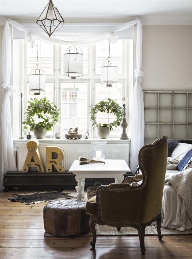 Mycket ljus. Fönstret i vardagsrummet ger ett fint ljusinsläpp. De gula plåtbokstäverna är köpta via en nätauktion. De står på en snidad träsockel som egentligen är en överdel till ett gammalt skåp.