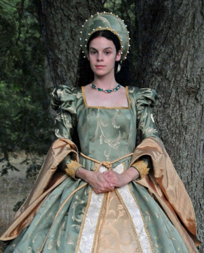 middle age hairstyles, woman with straight dark hair, wearing a green headdress, decorated with pearls, and a dress in the same color, with large sleeves, and golden details