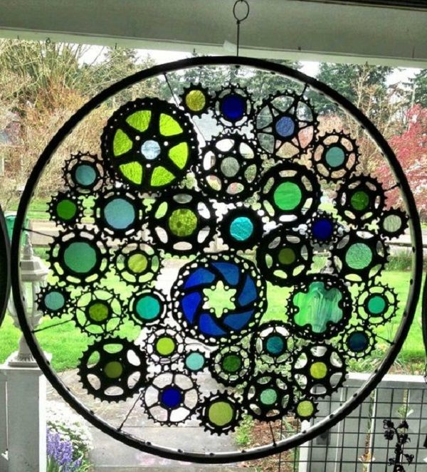 """Recycled Bicycle Wheel Stained Glass Hanging Panel by Brian Echerer. A 27"""" wheel with welded stained glass bike cogs and gears suspended by bicycle spokes in an old bike rim. www.custommade.com"""