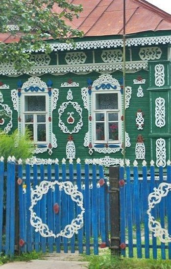 Russian wooden house and a wooden fence. They are decorated with openwork carving.