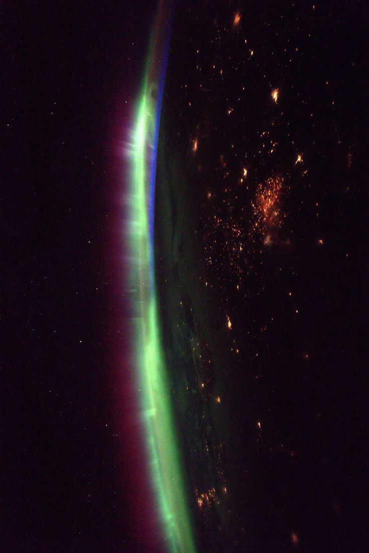 Aurora glowing on Earth's horizon with nighttime lights visible below