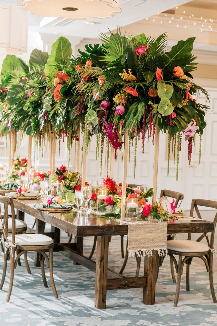 Tropical garden wedding centerpiece with palm leaves & fronds.  Wood farm tables…