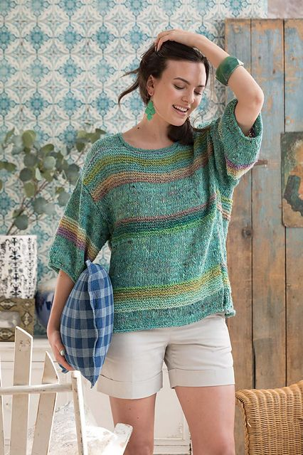 The bright turquoise and placid pastels of this short-sleeve pullover—which drapes divinely thanks to its relaxed gauge—evoke a shimmering pool. Rolled edges at the neckline, cuffs and split hem, an airy fit and loose-fitting sleeves keep it cozy. Knit in Silk Garden Sock Solo #31 Forest, the solid stockinette background sports textured garter-stitch bands in Silk Garden Sock colorway #437 Penelope's Garden.