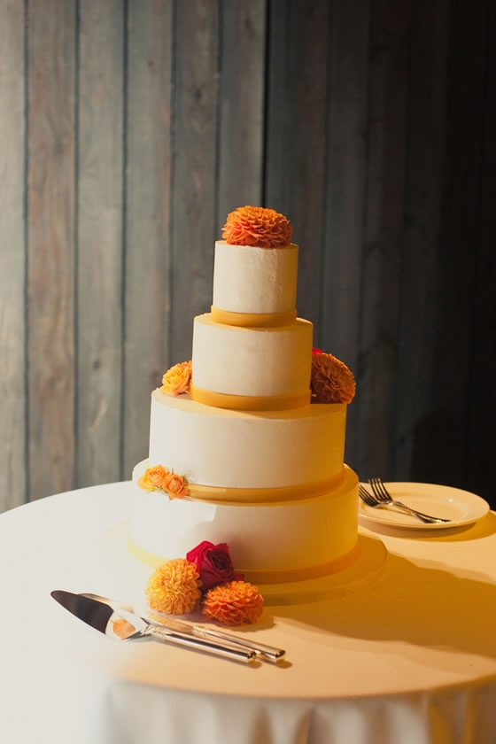 A big orange dahlia and orange fondant bands around each tier of this white wedding cake.