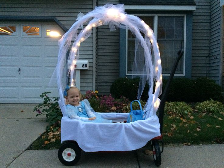 Cinderella's Carriage... I created this to go along with my daughter's costume. I used a Radio Flyer wagon with seat backs, two tent poles (crossed and cable tied), white fleece (wrapped outside of wagon and poles), roll of white tulle, and battery LED lights.