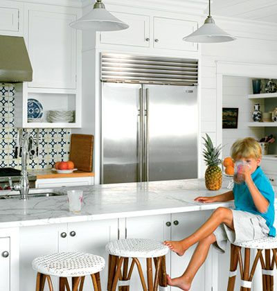 White, coastal kitchen on Cat Island in South Carolina with white Carrara marble countertops, sleek white cabinets, and a blue-and-green patterned, tile backsplash