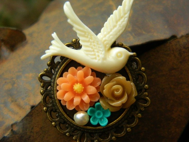 A vintage style resin and metal alloy brooch. Resin flowers and swallow, a Swarovski crystal pearl and metal alloy brooch in a antique bronze tone. Width 4.5 cm, depth 1 cm.   Custom orders are welcome, the colour of the flowers can be varied, with the addition or removal of pearls  https://www.madeit.com.au/Main/Item?itemId=956775