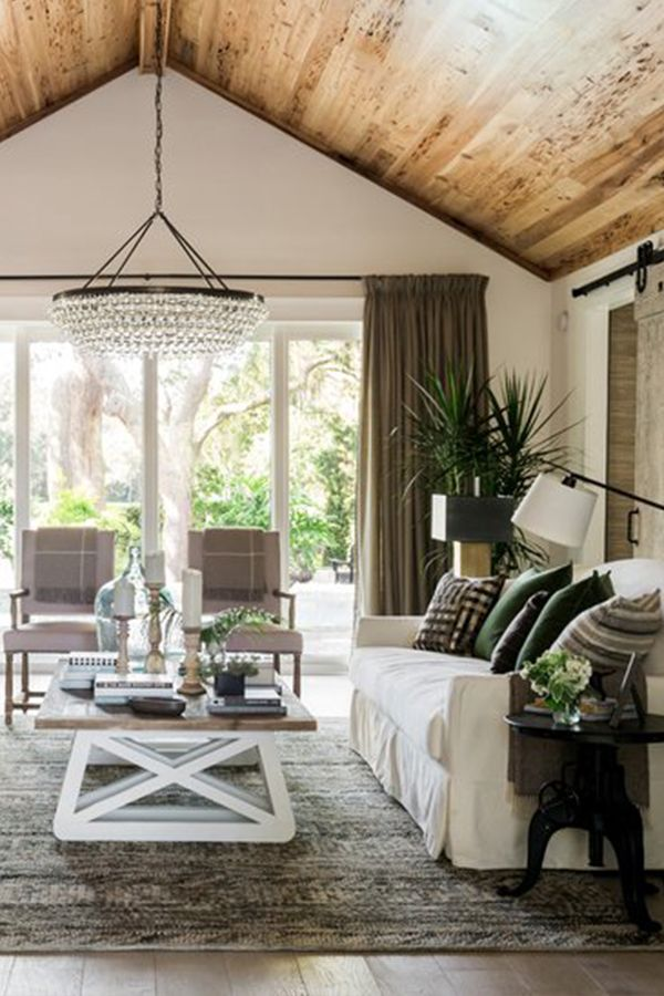 Introducing the HGTV® Dream Home 2017: Peek inside this Southern-inspired seaside home, furnished by Wayfair. In this living room, casual white sofas, cozy throws, and accent pillows in metallics, browns, and dark greens invite guests to make themselves at home and relax, while a cool chandelier and structured armchairs up the ante. The layered wooden finishes and tones of the peaked ceiling panels, coffee table, and trendy sliding barn door provide consistency.