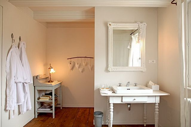 french country inspired white bathroom with old weathered wooden floors & vanity nook