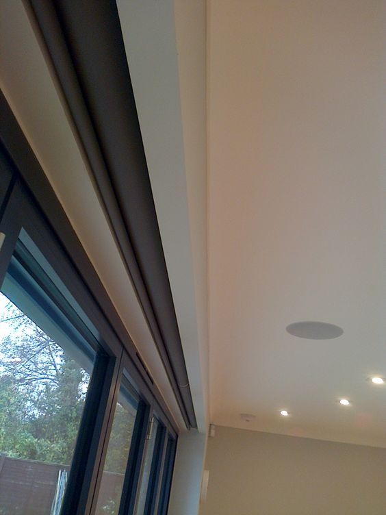 Electric Blinds covering Bifold Doors hidden with in a recess in the ceiling by Deans Blinds & Awnings: