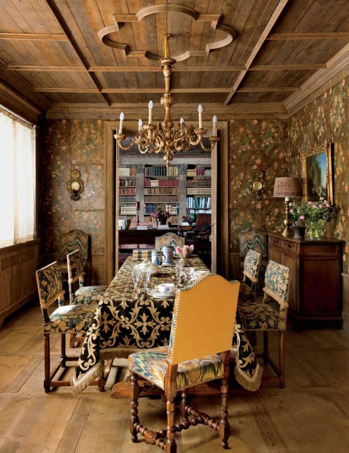 decoracion de comedores, comedor con mesa rectangular, mantel en negro y oro, sillas tapizadas, lámpara de araña, parqué, librería