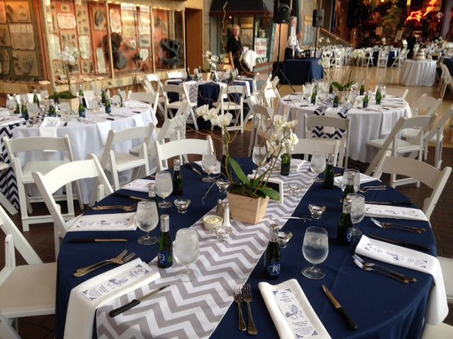 Beautiful table scape using phalenopsis orchids designed by Eastern Floral for a wedding at the Grand Rapids Public Museum. Navy blue and Grey chevron linens really make this table beautiful!