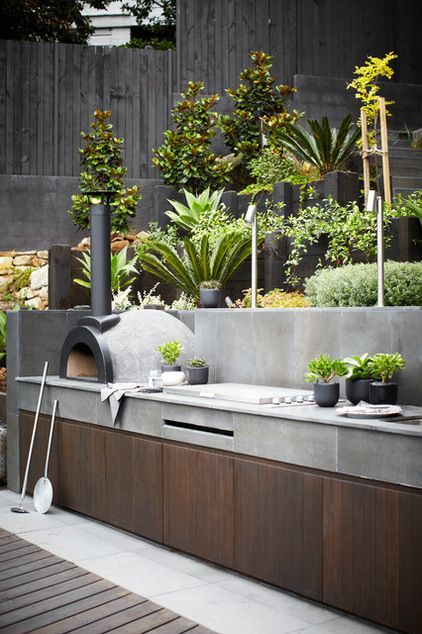 this is ridiculously pleasant...Go modern. Concrete and rich wood are a modern minimalist pairing perfect for an urban environment. This outdoor kitchen is outfitted with a pizza oven — a worthy splurge if you love doing a weekly pizza night at home!