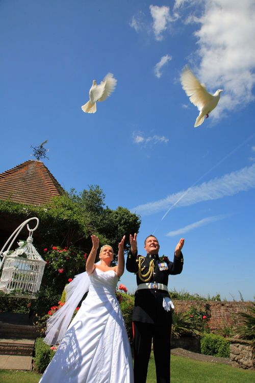 Bride and groom letting doves fly