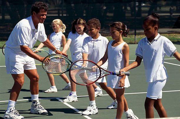 Man Teaching A Group Of Children Tennis Techniques Picture Tennis Picture New Tennis Racket Tennis Drills Tennis Best Tennis Rackets Tennis Clothes Tennis