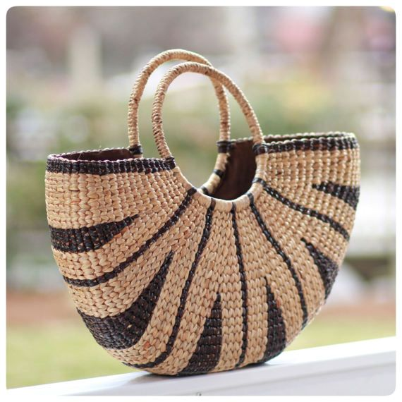 Our handwoven tribal tote is made from seagrass and features a natural rounded handle with a tribal design.  Measurements:  19 W (left-to-right) x 11 H (top-to-bottom) x 4 D This gorgeous handwoven tote with tribal design you can carry your essentials to the beach or any outdoor event. The tote is wrapped with a rounded handle. The tote can fit all your essentials for an outdoor picnic and take it with you on your picnic or beach day. This is a unique product. All of our bags are made from…