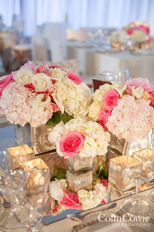 Arrangements of peonies, hydrangeas, and roses in mercury glass vessels sit atop a mirrored surface to create a glamorous feel.
