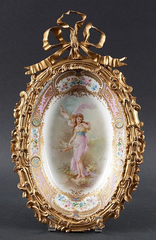 """<b>French Sevres ormolu-mounted painted porcelain plaque</b> <br /> 19th century; signed A. Collott,"""" porcelain with central scene of Venus and Cupid and parcel-gilt floral border, Sevres type mark underneath, scroll-form ormolu mounts with large bow, 16 in. L. total"""