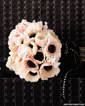 A tailored yet poetic bouquet of anemones, with their true-black centers and white sweet peas, is cinched with a wide black-velvet band and narrow dotted ribbon.