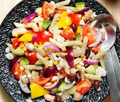 Denna grekiska sallad med fetaost, oliver och rödlök är en sommarfräsch lättare lunch. Pastan och de vita bönorna bidrar till en mer mättande känsla. Dressingen med vitvinsvinäger och oregano gör salladen extra god. Bra att ta med på picknick.